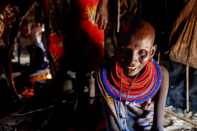 a woman with a red and blue necklace sitting inside her hut