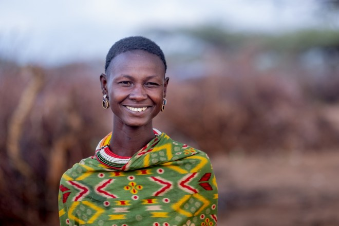 a woman in a green patterned top smiling at the camera in Kenya