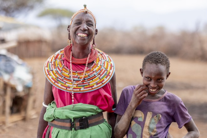 a grandmother and granddaughter standing next to each other and smiling