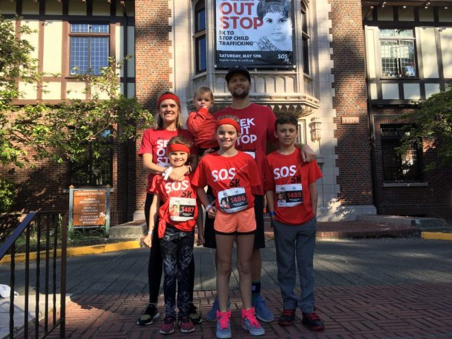 a family poses for a photo during a 5k race to stop child trafficking