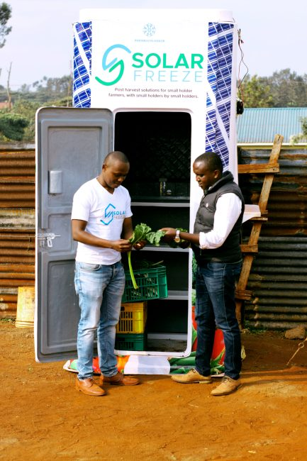 Two men stand in front of the Solar Freeze solar-powered fridge, holding fresh produce.