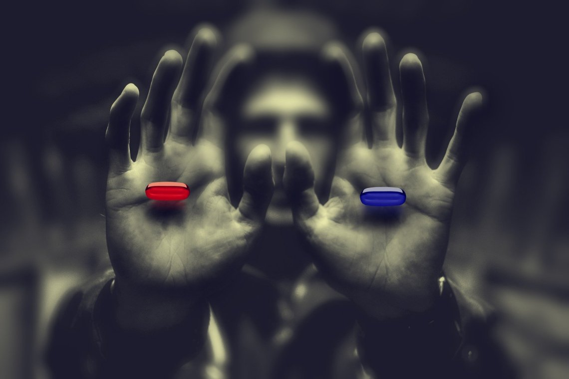 blurred hooded man in background with his hands in the foreground with a red pill in one and blue pill in the other