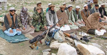 Taliban fighters with weapons praying in the open