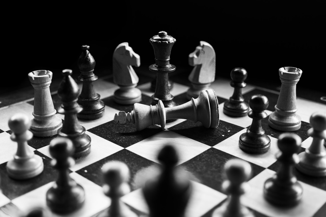 toppled king surrounded by other pieces on chessboard. In black and white
