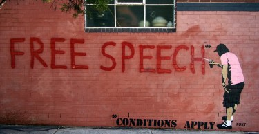 grafiti of words 'free speech conditions apply' on wall
