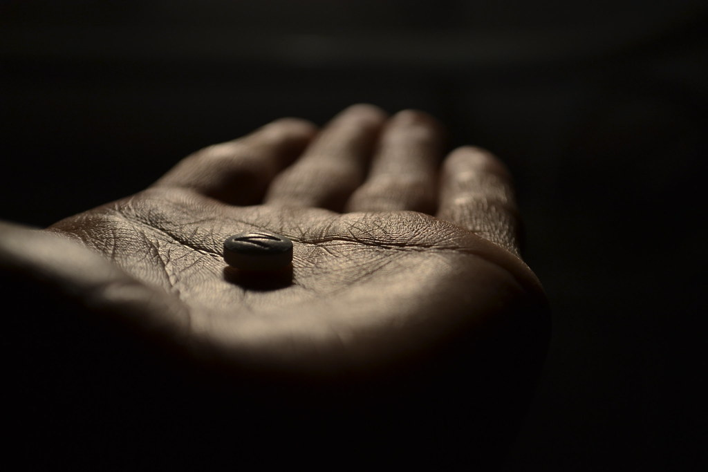 close up of hand with a single pill. Very dark background
