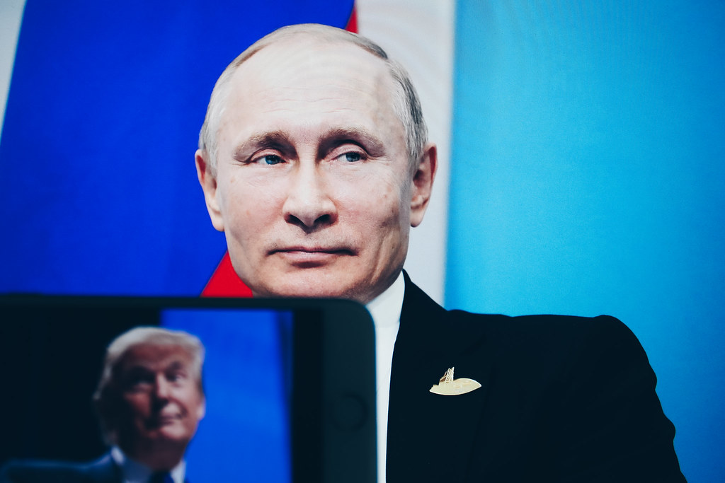 Putin with screen in foreground featuring trump