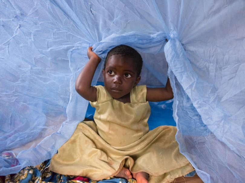 young girl lifting mosquito net