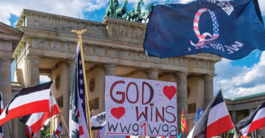 qanon flag and christian signs at Maga protest