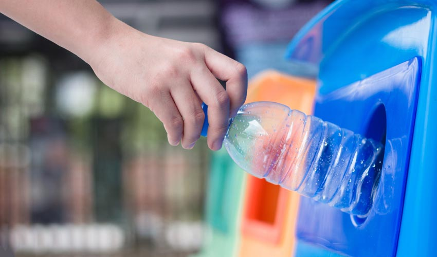 hand putting plastic bottle in to recycling bin