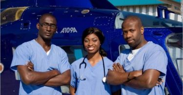 3 nigerian doctors next to helicopter