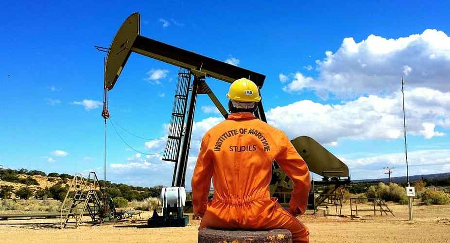 african oil worker sat in front of oil well