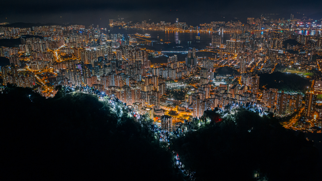 Pro-democracy citizens form human chains and shine their mobile phone light as they gather on the top of Lion Rock against the night view of Hong Kong to highlight their protest on extradition bill. They were inspired by a historic protest 30 years ago in the Baltic states against Soviet control.