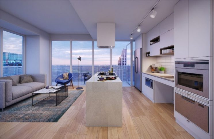 rendering of a condo suite showing the living room and kitchen separated by an island, showing generous clearances, lowered appliances, under-sink knee clearance, and a roll-out balcony