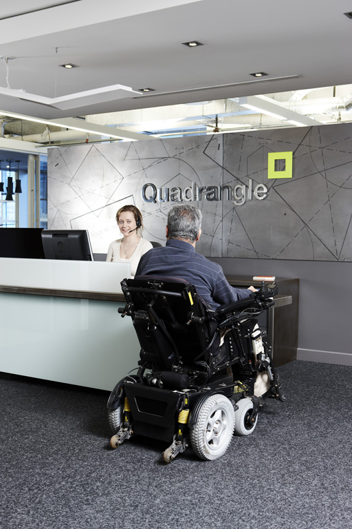 man in a wheelchair speaks to the Quadrangle receptionist