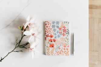 notebook with pen near white magnolia flower
