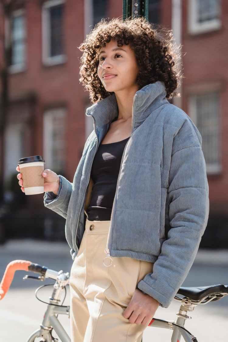 positive young ethnic woman enjoying takeaway coffee on street