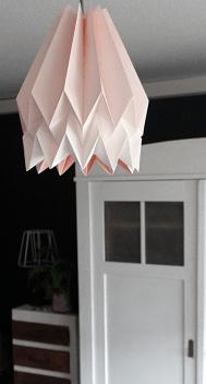 zu sehen ist eine roséfarbene Origamilampe und ein Vintageschrank