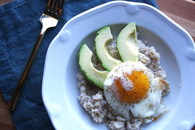 fried egg on top of oatmeal with avocado