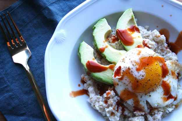 savory oatmeal with a fried egg, avocado, and topped with chipotle cholula