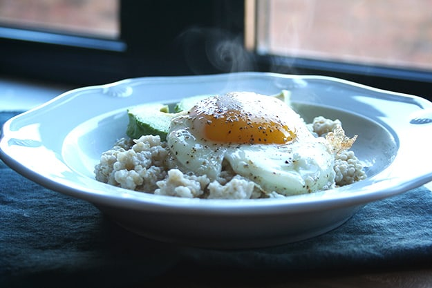 savory breakfast oatmeal topped with avocado and a steaming fried egg