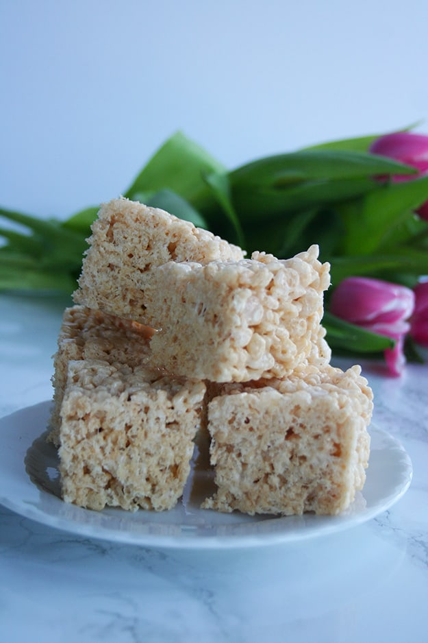 a plate of browned butter Rice Krispie treats perfectly centered with pink tulips out of focus in the background