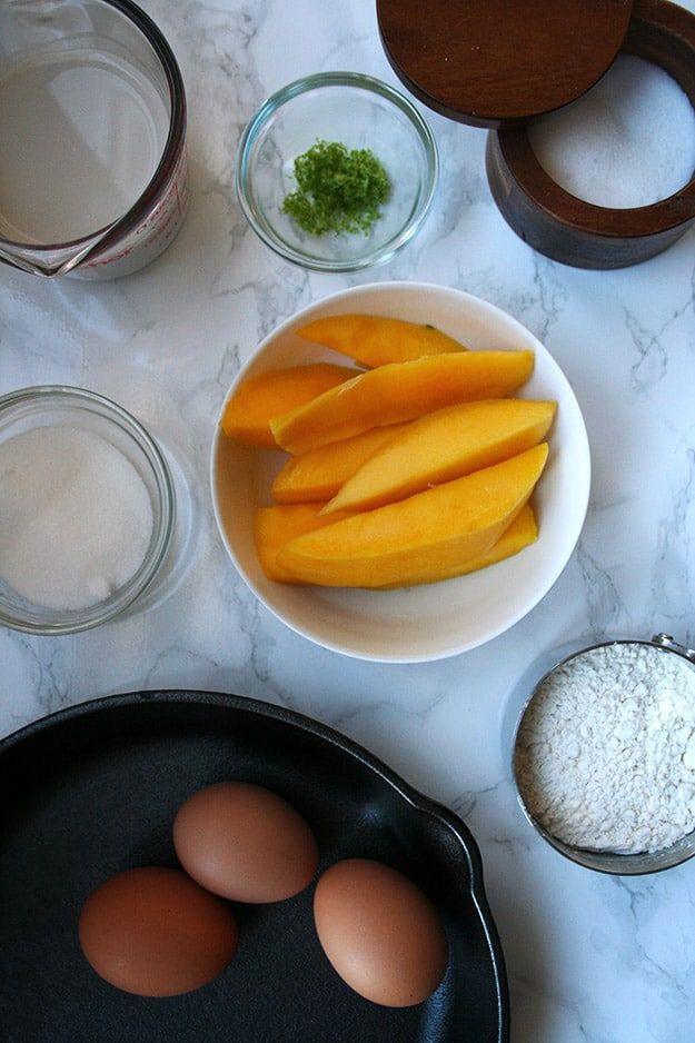 all the ingredients for the mango lime dutch baby - eggs, flour, sugar, almond milk, lime zest, salt and mango