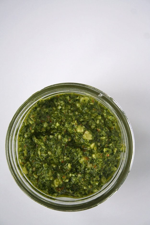 an overhead shot of this ultra green kale almond pesto in a glass jar on a blank white canvas