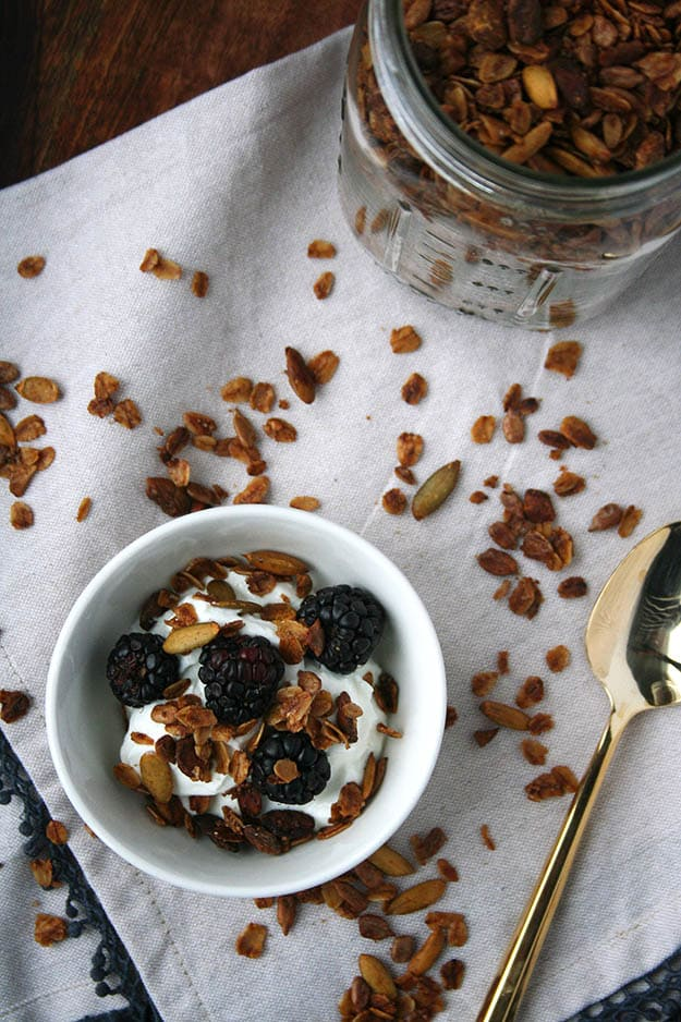 an overhead shot of greek yogurt topped with blackberries and olive oil pistachio granola on a cream napkin covered in granola sprinkles with a glass ball jar filled with olive oil pistachio granola
