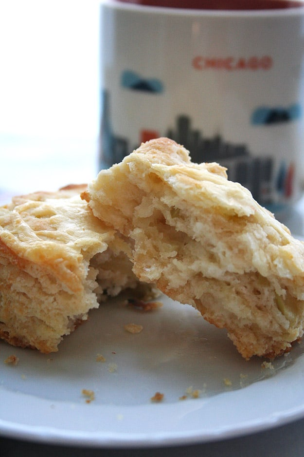 layers of flaky and buttery Granny Smith apple and white cheddar scones on a white plate with a Chicago coffee mug in the background