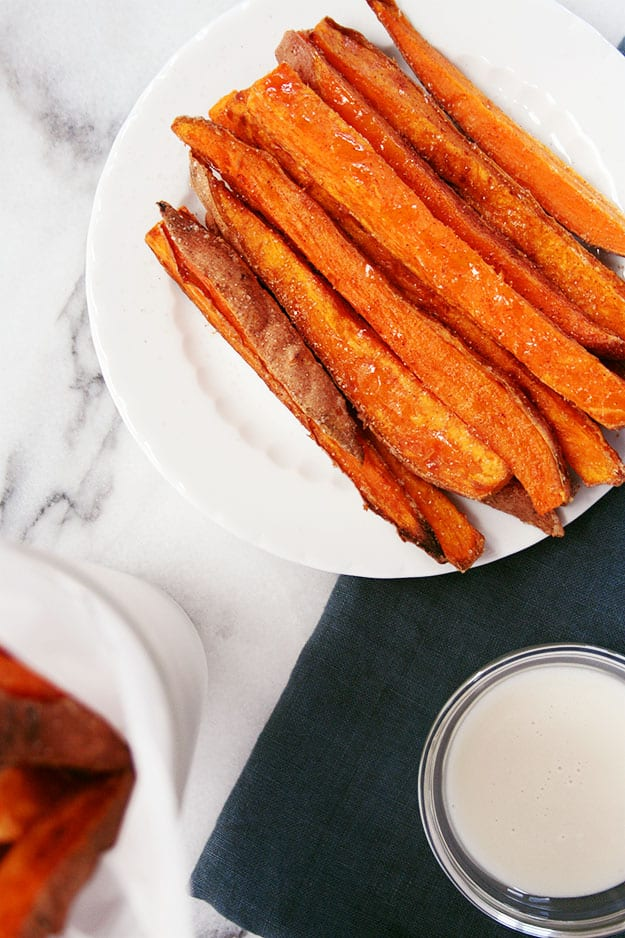 sweet potato fries topped with cinnamon sugar and a bowl of vanilla glaze for dipping on a navy napkin and carrara marble