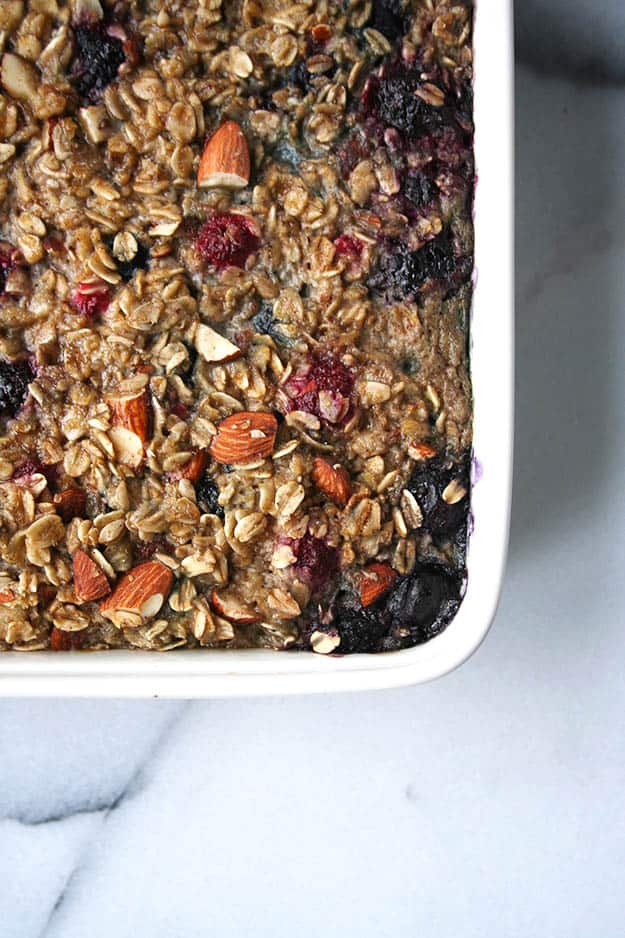 an zoomed in overhead shot of triple berry baked oatmeal in a while ceramic baking dish on cararra marble