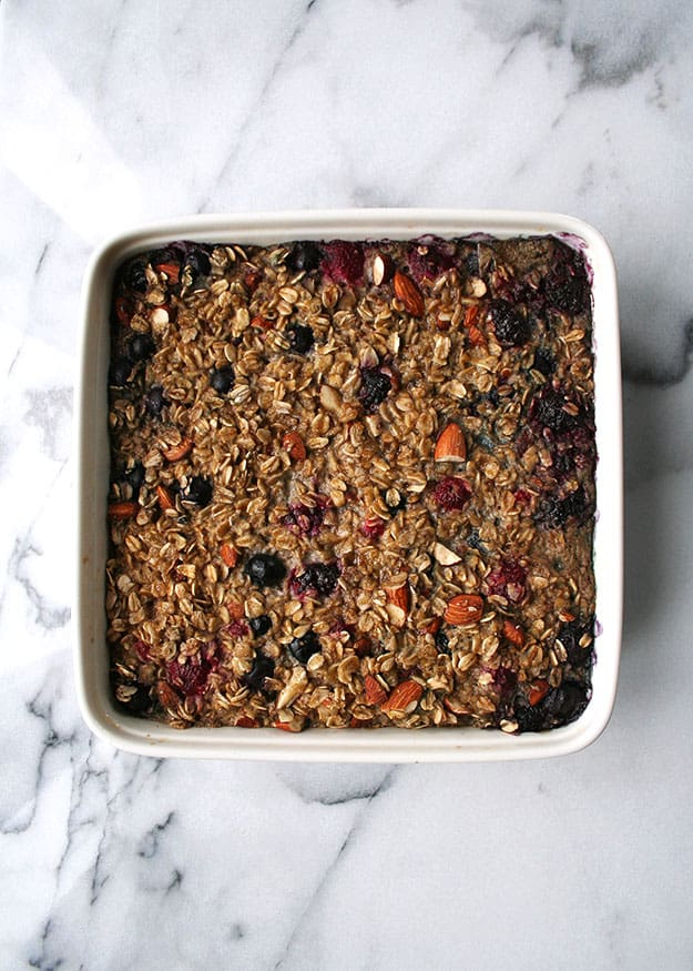 a zoomed out overhead shot of raspberry, strawberry and blueberry baked oatmeal in a while ceramic baking dish on cararra marble sprinkled with almonds