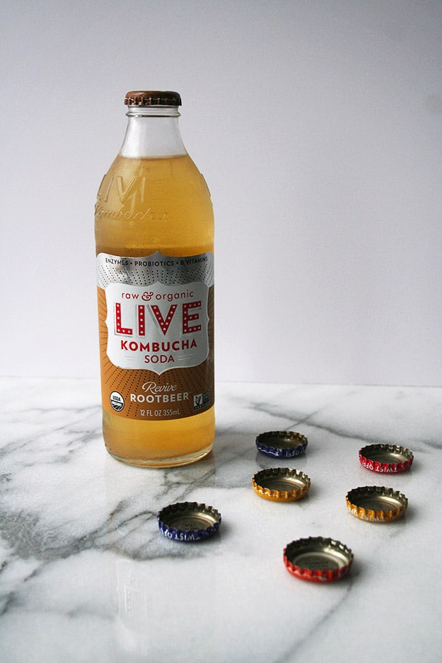 a bottle of root beer flavored LIVE kombucha soda on a carrara marble counter scattered with bottle tops
