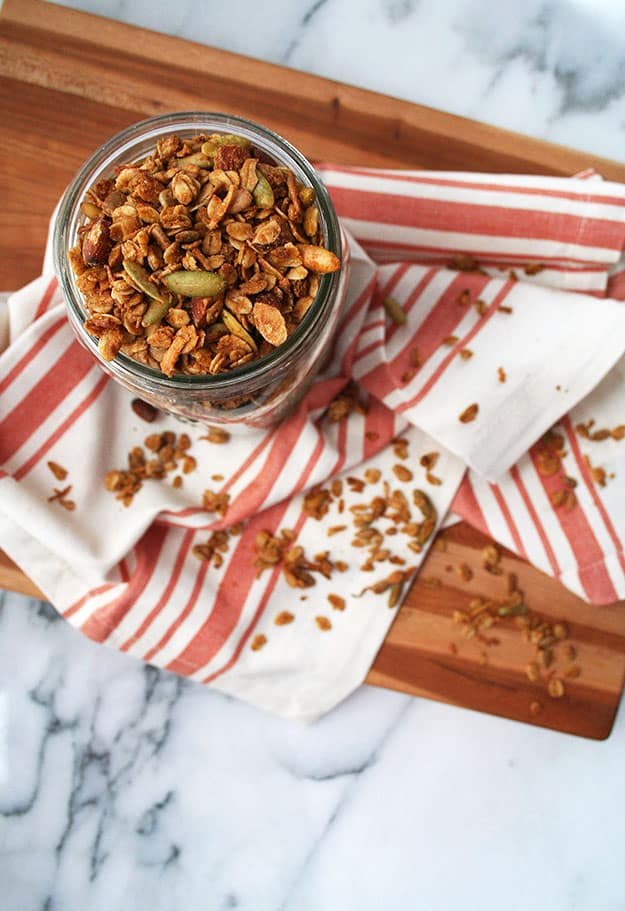 an overhead shot of an in focus glass Ball jar full of maple tahini granola in the foreground and a cream and orange striped napkin and wooden cutting board out of focus in the background