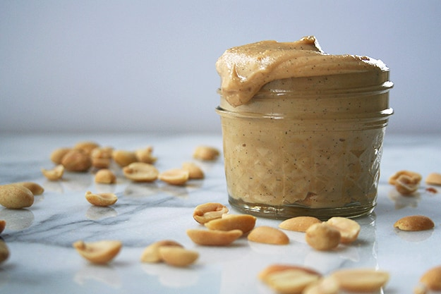 a jar of homemade honey peanut butter speckled with vanilla beans dripping down the side on a marble counter sprinkled with peanuts