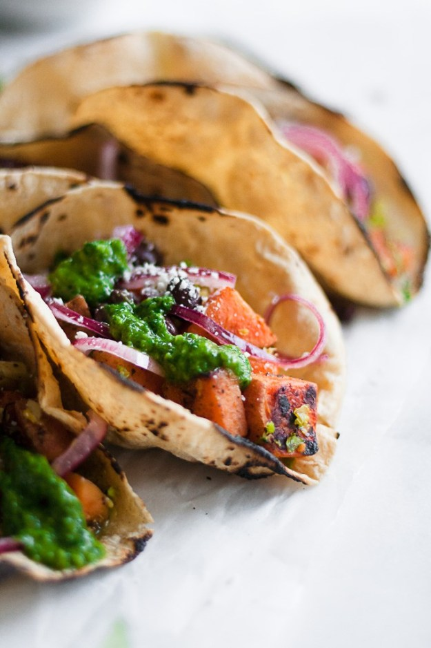 close up shot of sweet potato and brussels sprout tacos in charred corn torillas sprinkled in cojita cheese, chimichurri sauce, and pickled red onions