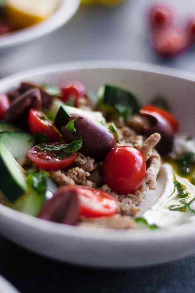close up shot of a bowl filled with plain greek yogurt, Mediterranean spiced ground turkey, sliced tomatoes, cucumbers and olives, fresh mint and a drizzle of olive oil
