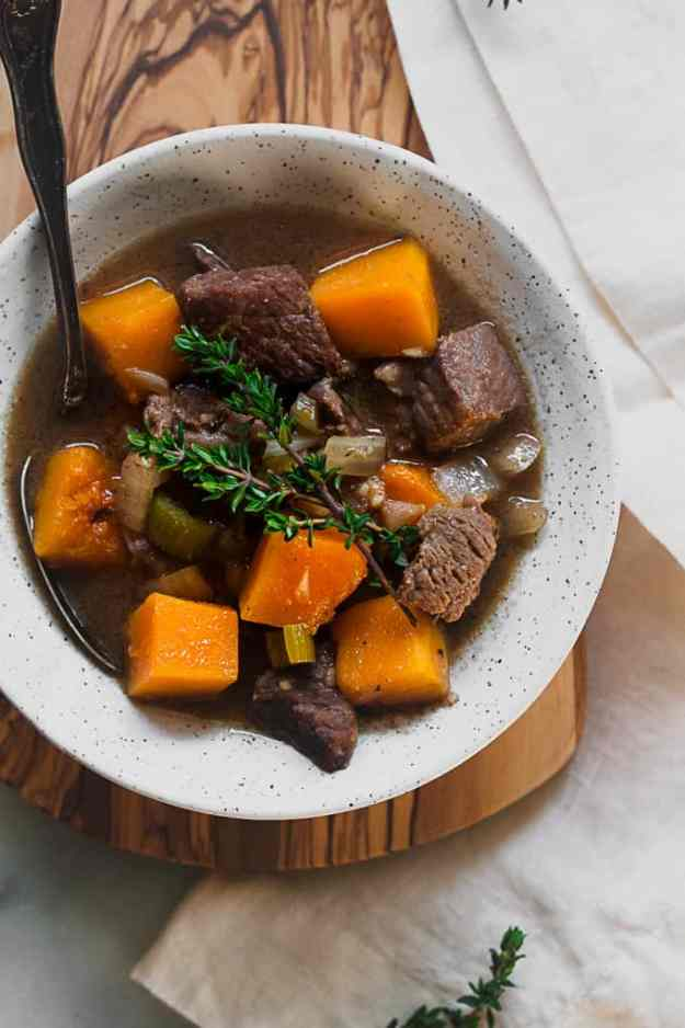 overhead shot of butternut squash and beef stew in a bowl on top of a cutting board and marble counter with linen