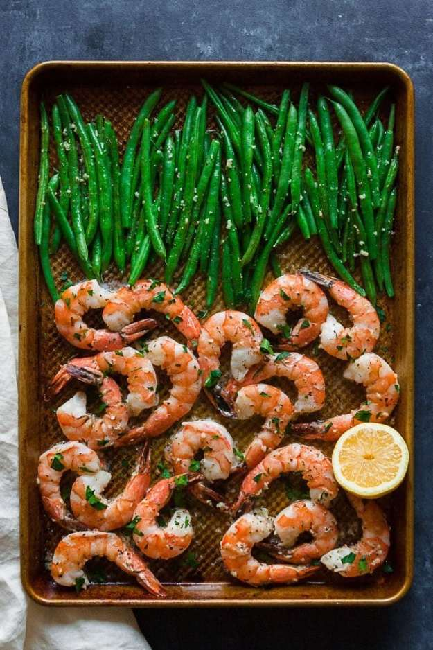 overhead shot of sheet pan shrimp and green beans on a blue backdrop with a cream napkin