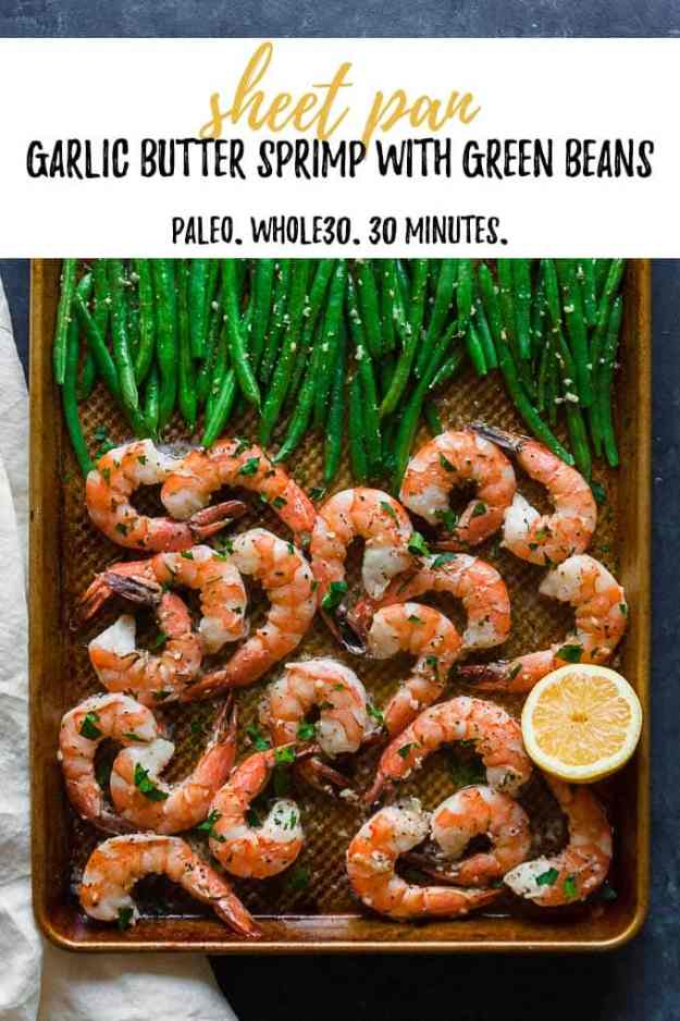 overhead shot of sheet pan shrimp and green beans on a blue backdrop with a cream napkin with text overlay