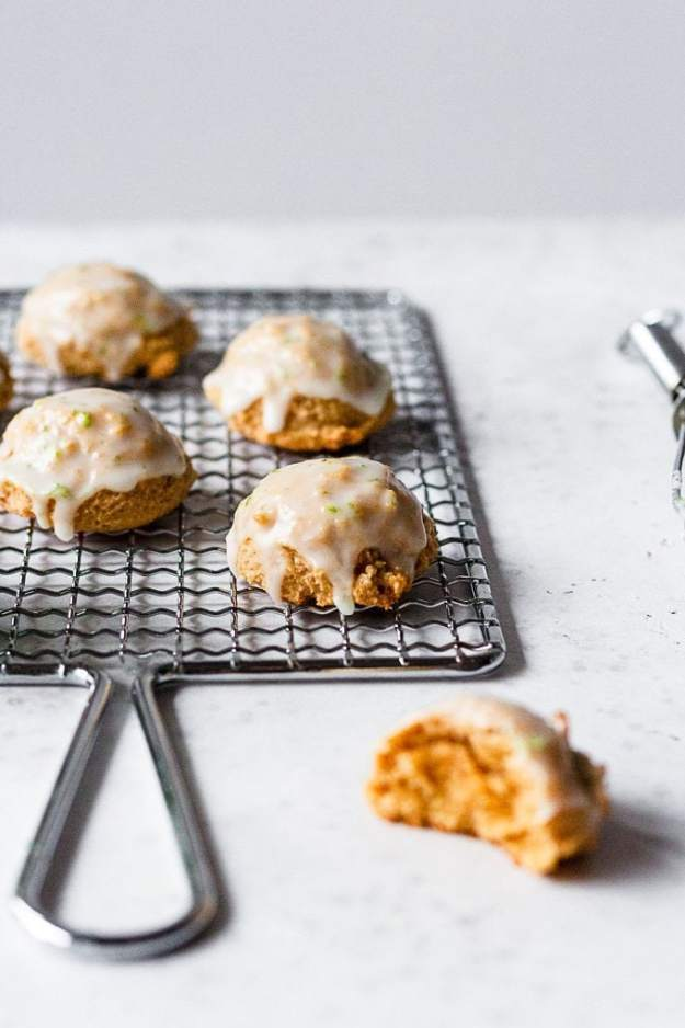 coconut lime cookies with tequila drizzle on a drying rack with glaze dripping and a half eaten cookie