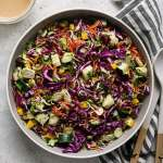 chopped thai brussels sprout salad in a serving bowl with dressing on the side