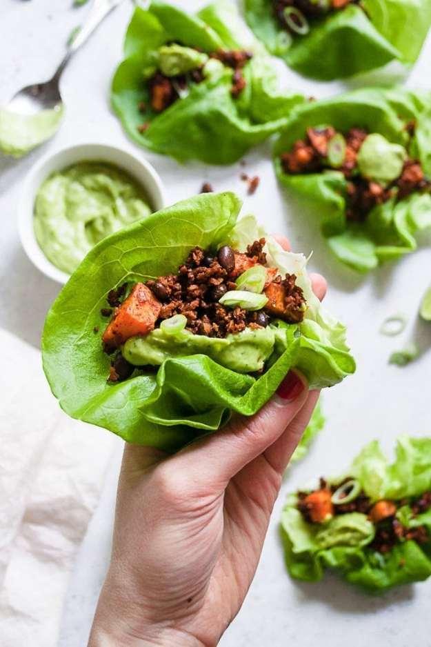 a single hand holding a soy chorizo lettuce wrap