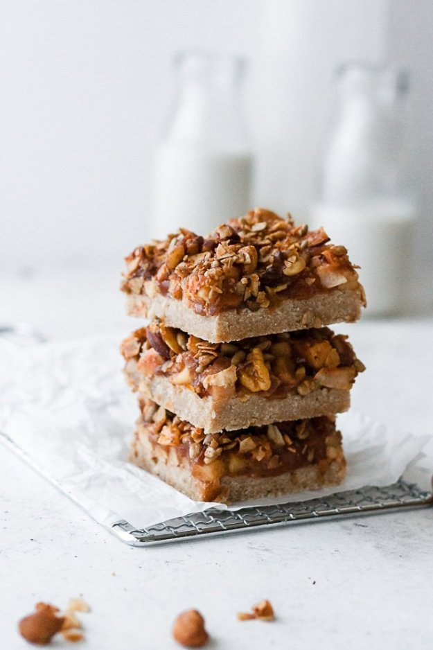 stack of three gluten free apple pie bars on parchment paper and cooling rack