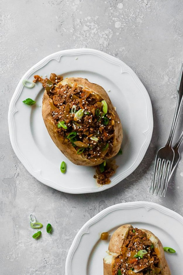 whole30 korean sloppy joes in baked potatoes on a white plates topped with sesame seeds and scallions
