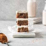 stack of three raw vegan carrot cake bars with cashew cream cheese frosting