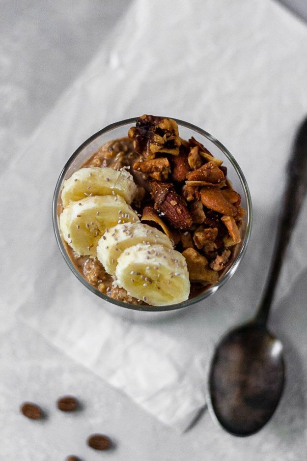 overhead shot of espresso overnight oats with banana slices and granola in a glass