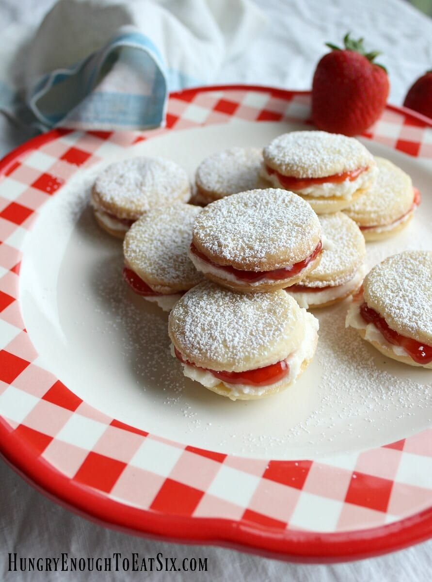 Rich and simple homemade shortbread cookies hold a sweet filling of lemon buttercream and strawberry jam.