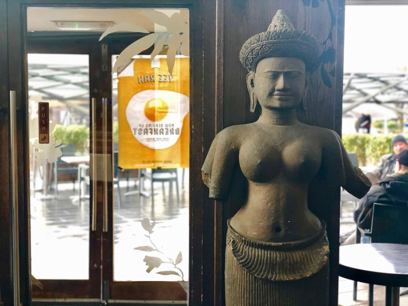 Traditional Thai stone statue in front of a brown door with glass panels at Yee Rah restaurant in Liverpool ONE